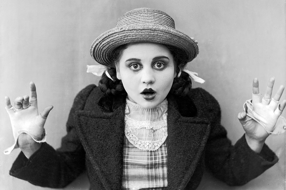 circa 1915:  American actor Bebe Daniels holds up her hands and opens her mouth in surprise, in a still from an unidentified silent film. She wears a straw hat and fingerless gloves with her hair in pigtails.  (Photo by American Stock/Getty Images)